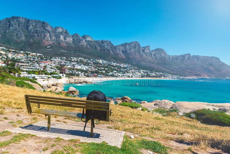 Le sac à dos du voyageur seul sur un banc avec vue sur des camps aboient belle plage à Cape Town image libre de droits