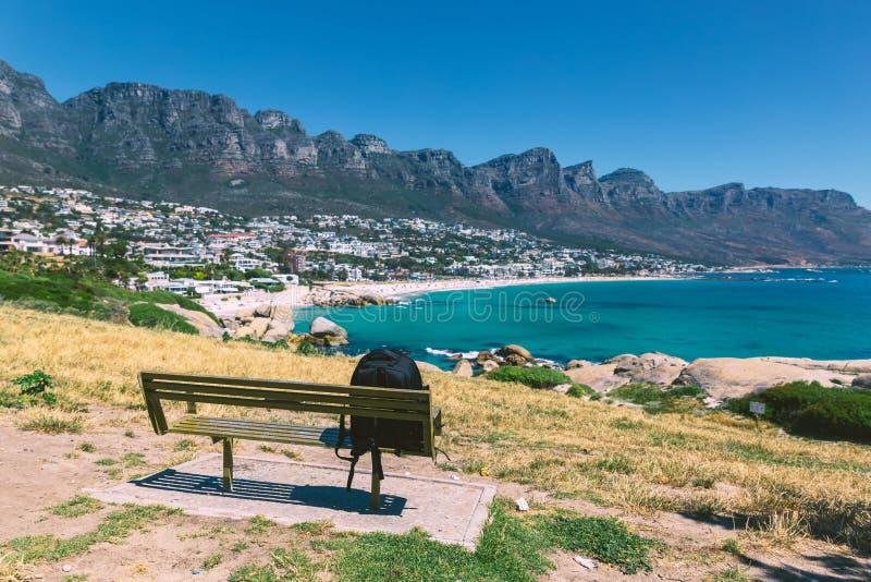 Le sac à dos du voyageur seul sur un banc avec vue sur des camps aboient belle plage à Cape Town photographie stock libre de droits