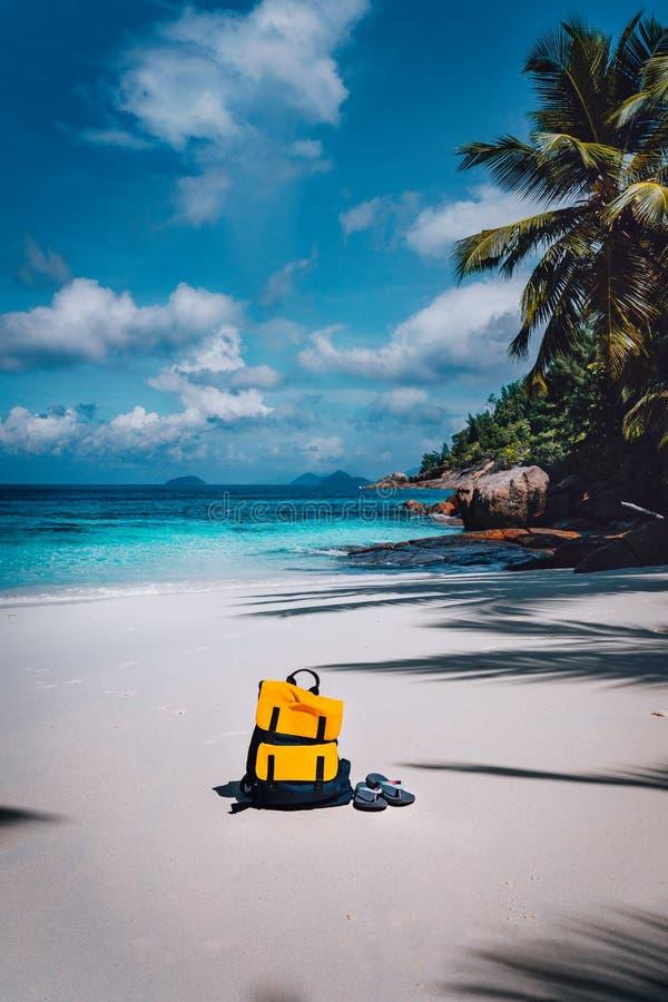 Le sac ? dos jaune de voyageur et les bascules ?lectroniques sur la plage tropicale ar?nac?e des vacances d'?t? se d?clenchent, v photographie stock libre de droits