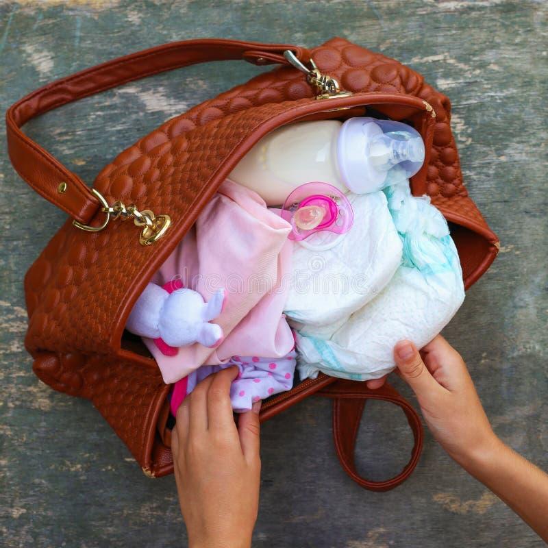 Le sac à main de la mère avec des articles à s'occuper de l'enfant sur le vieux fond en bois photos libres de droits