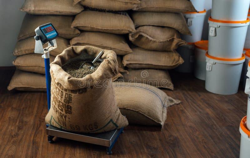 Le sac Burlap avec des haricots à café et un scoop en métal se trouve sur une balance photographie stock libre de droits