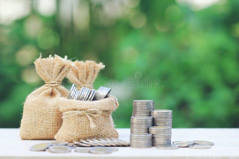 Le sac d'argent avec la pile d'argent de pièces de monnaie sur le fond vert naturel, économie pour préparent dans le concept d'av photographie stock