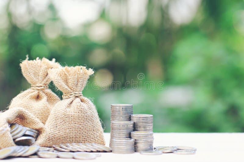 Le sac d'argent avec la pile d'argent de pi?ces de monnaie sur le fond vert naturel, ?conomie pour pr?parent dans le concept d'av photographie stock libre de droits