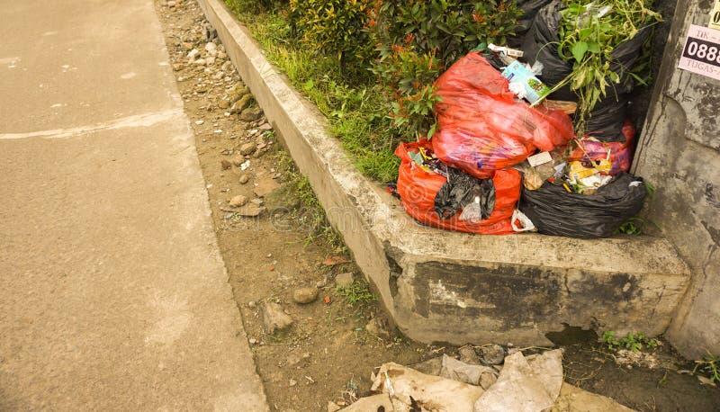 Le sac de déchets en plastique dans le trottoir utilisant le rouge met en sac le depok rentré par photo Jakarta Indonésie photographie stock libre de droits