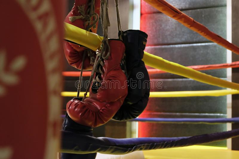 Le sac de sable et les gants de boxe rouges accroche outre du ring images stock