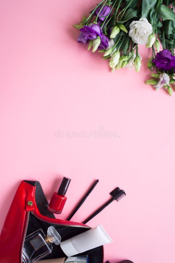 Le sac des femmes avec des accessoires sur pâle - fond rose image stock