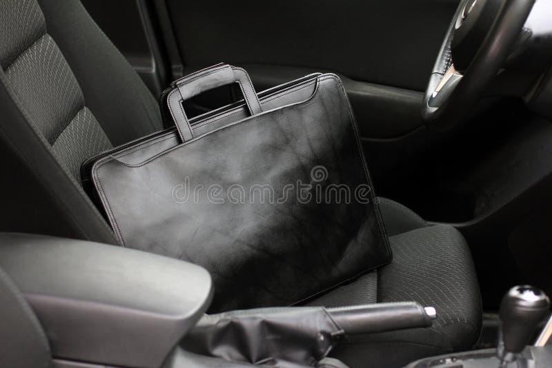 Le sac en cuir noir élégant d'homme d'affaires sur le siège de rdiver dans la voiture avec l'intérieur moderne images stock