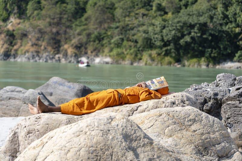 Le sadhu indien, homme saint se repose un jour ensoleillé chaud sur les banques de la rivière Ganga dans la ville de Rishikesh, I photo stock