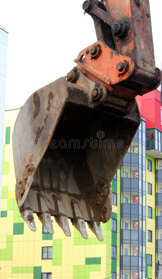 le sale travail du seau d'excavatrice, qui creuse et a nivelé les scoops moulus arrosent sur des réparations de route images libres de droits