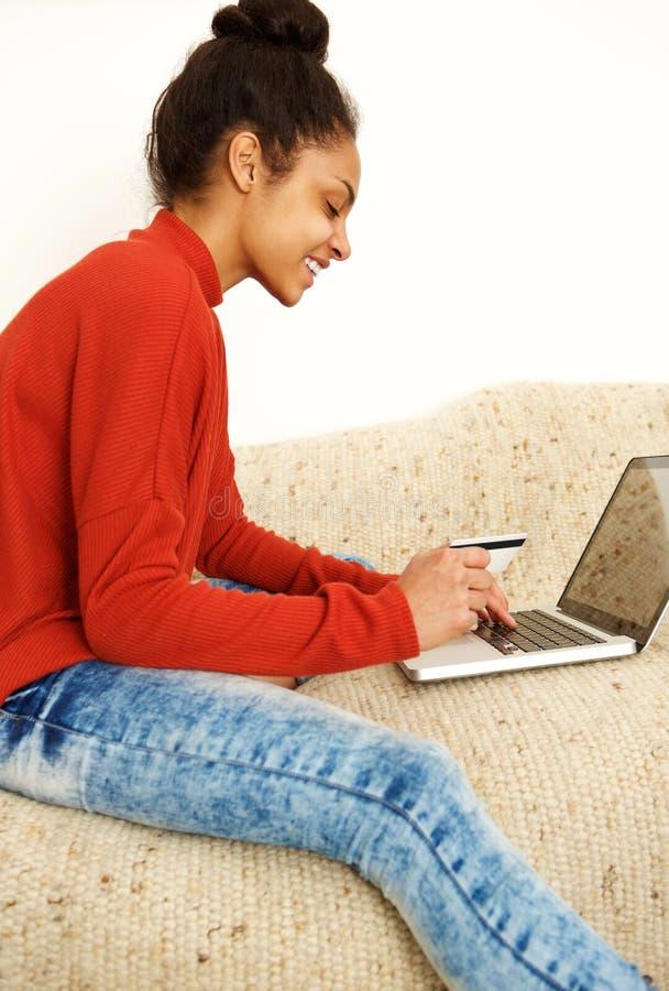 Le sammanträde för ung kvinna på soffan med bärbara datorn och kreditkorten royaltyfria foton