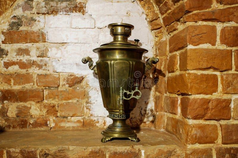 Le samovar de cuivre antique se tient sous forme de paysage sur le fond du mur de cheminée de la brique rouge Fond, rétro, image stock