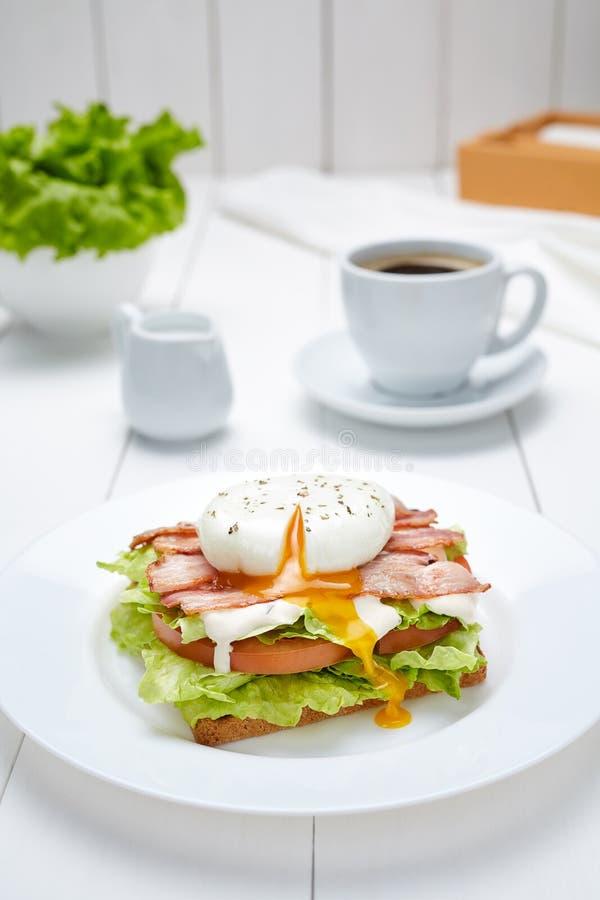 Le sandwich à oeufs pochés avec le lard, salade, mayonnaise, tomates, a grillé le pain image libre de droits