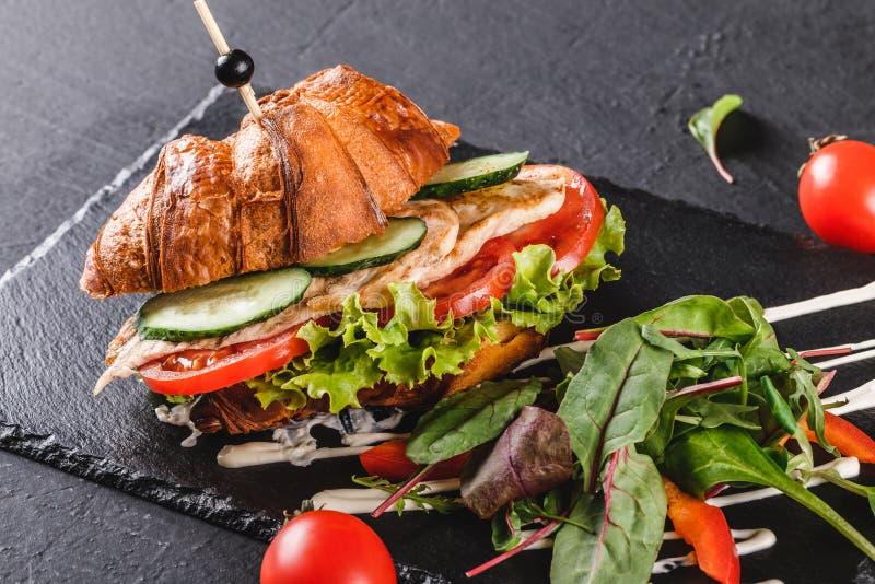 Le sandwich ? croissant avec le filet a grill? le poulet, les l?gumes frais, le fromage et les verts sur le panneau de schiste no image libre de droits