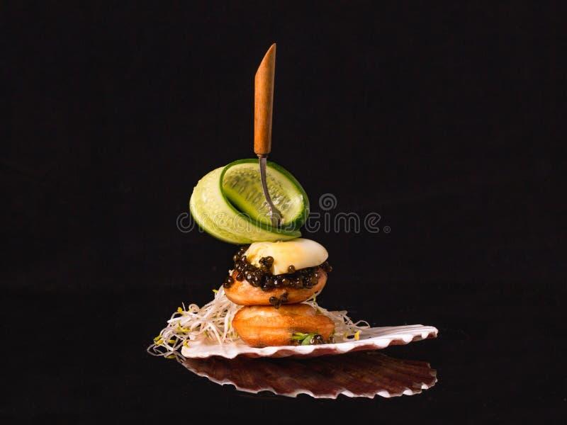 Le sandwich du caviar noir avec des poffertjes, oeuf de caille et concombre, a servi dans une cuvette de coquille photographie stock libre de droits