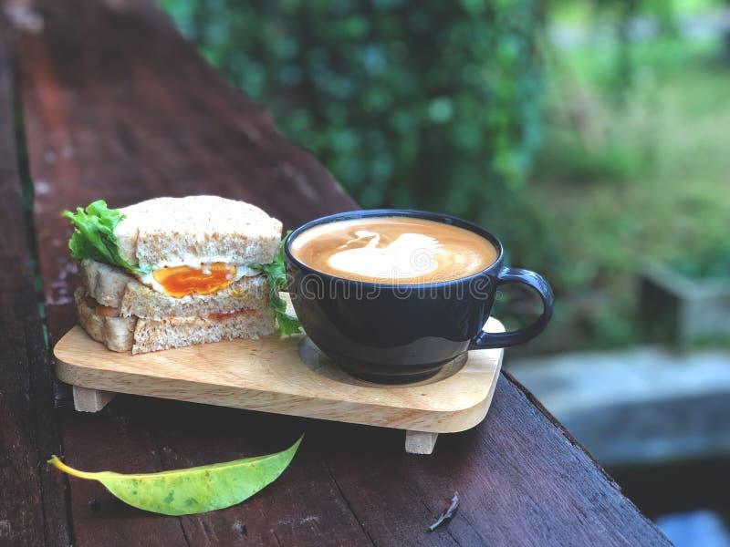 Le sandwich et le cygne frais forment la tasse de café d'art de Latte sur la table en bois photo stock