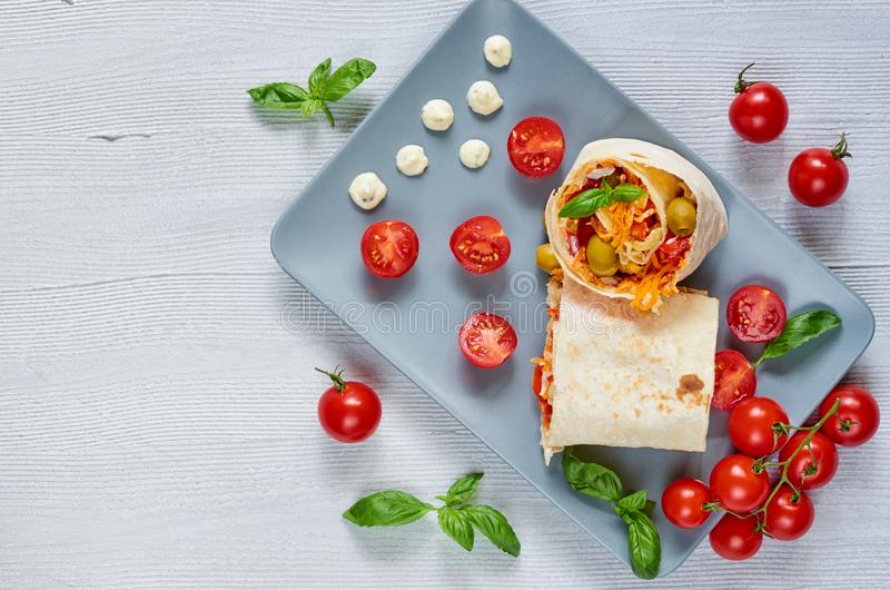 Le sandwich ou le lavash à Shawarma avec les légumes frais et la sauce du plat gris decotated avec des tomates-cerises, basilic p images libres de droits