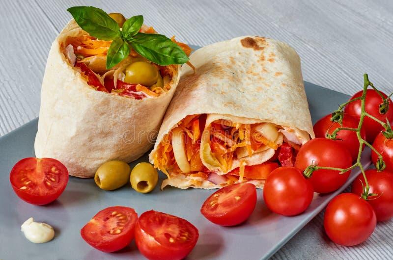 Le sandwich ou le lavash à Shawarma avec les légumes frais et la sauce du plat gris decotated avec des tomates-cerises, basilic p photographie stock