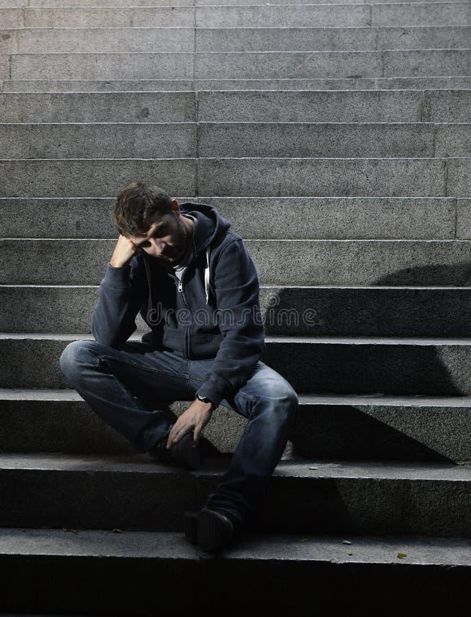 Le sans-abri de jeune homme a perdu le travail se reposant dans la dépression sur les escaliers moulus de béton de rue images libres de droits