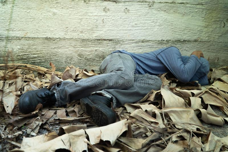 Le sans-abri a utilisé un chapeau gris et une chemise grise de long-douille Est sommeil en raison de l'épuisement, avec le dos le images libres de droits