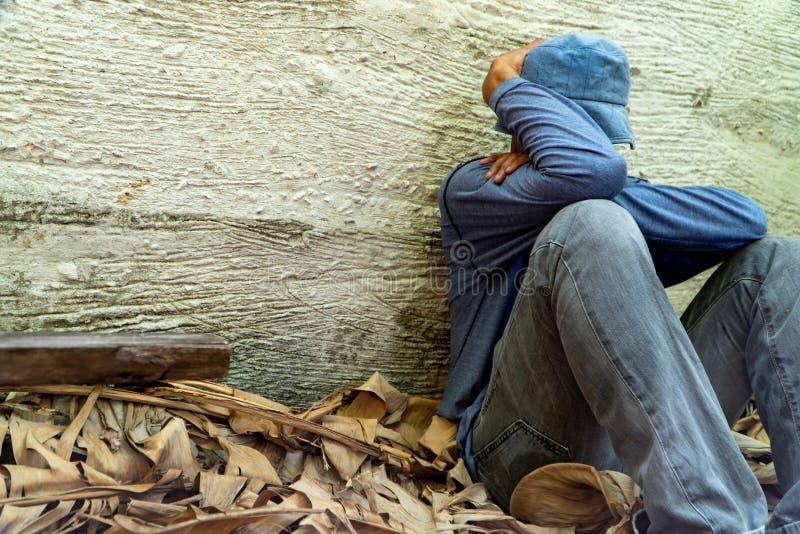 Le sans-abri a utilis? un chapeau gris et une chemise grise de long-douille Est sommeil en raison de l'?puisement, avec le dos le photo stock