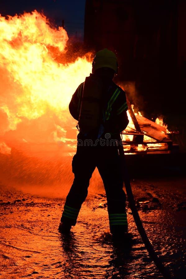 Le sapeur-pompier arrose vers le bas un feu au jet parmi les flammes fortes images stock