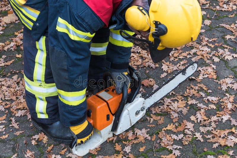 Le sapeur-pompier dans l'action et mettent en marche la tronçonneuse photo libre de droits