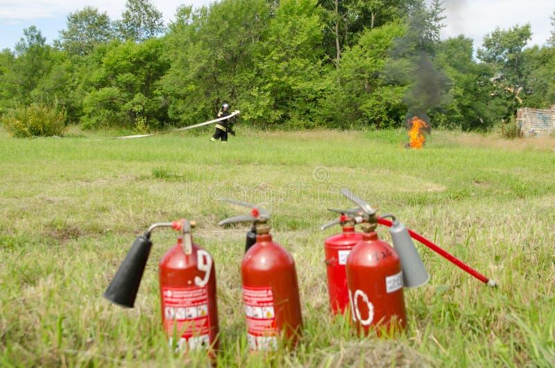 Le sapeur-pompier dispose à s'éteindre un pneu brûlant pendant le demonst image libre de droits