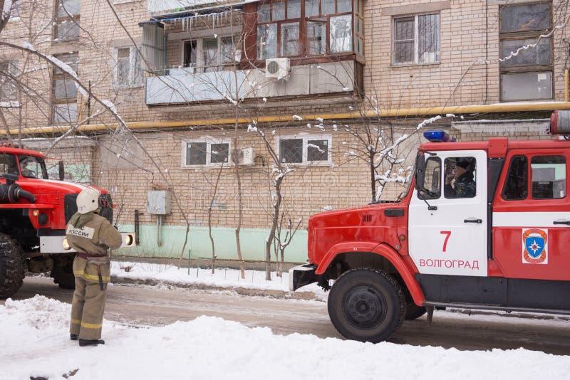 Le sapeur-pompier regardant un immeuble, près des pompiers, là sont deux machines photos libres de droits
