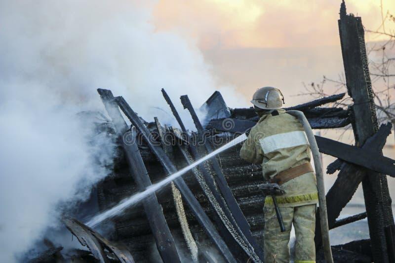 Le sapeur-pompier s'éteint le feu Pompier tenant le tuyau avec le wat images stock