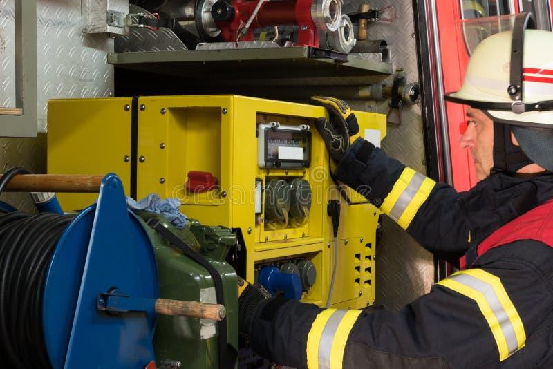 Le sapeur-pompier a utilisé le générateur de l'électricité sur le camion de pompiers photo libre de droits