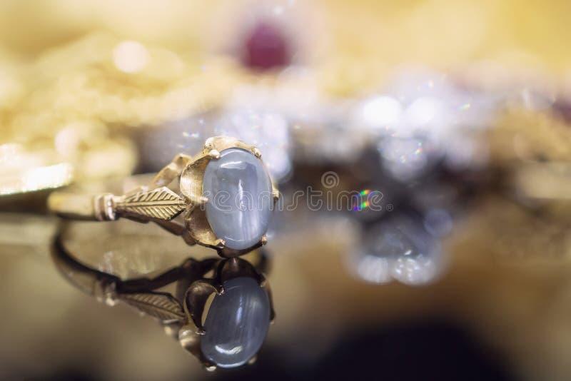 Le saphir bleu de bijoux d'or de vintage sonne avec la réflexion images stock