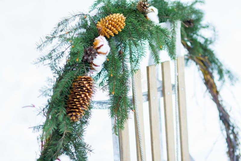 Le sapin de Noël et l'usine de coton tressent accrocher sur le traîneau en bois dehors image stock