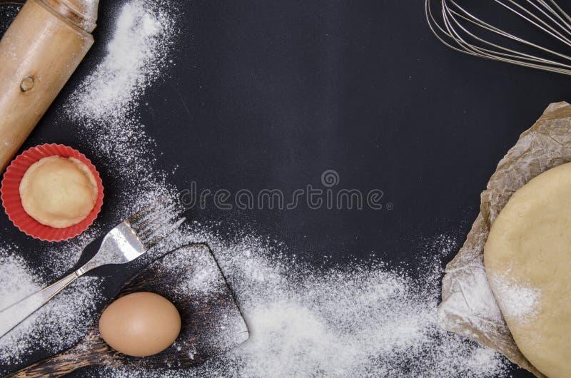 Le saupoudrage par la farine a déroulé la pâte pour le stics bakary avec la goupille en bois au-dessus du basground noir photographie stock libre de droits