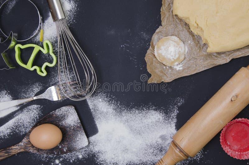 Le saupoudrage par la farine a déroulé la pâte pour le stics bakary avec la goupille en bois au-dessus du basground noir images libres de droits