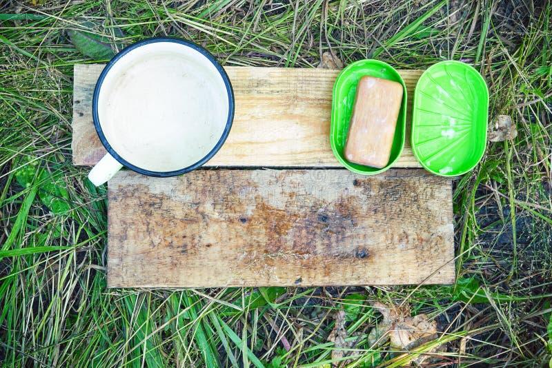 Le savon, le porte-savon et le lavage attaquent sur les conseils en bois sur le fond d'herbe photo stock
