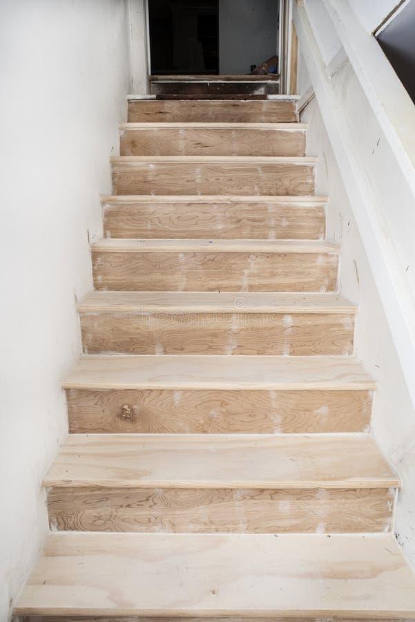 Le scale del seminterrato che vanno su, passi non finiti di legno nudo del pino, durante la casa ritoccano fotografia stock libera da diritti