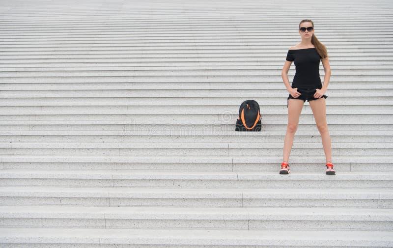 Le scale pietrose del supporto turistico della ragazza si avvicinano al suo zaino Aspetti per esplorare la nuova città Attrezzatu immagine stock