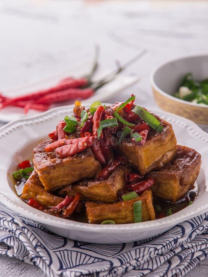 Le scalpore casalinghe hanno fritto il tofu con la salsa ed il peperoncino rosso di soia immagini stock libere da diritti