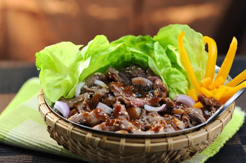 Le scalpore hanno fritto il manzo con le ostriche, la salsa e la lattuga in canestro di bambù fotografia stock