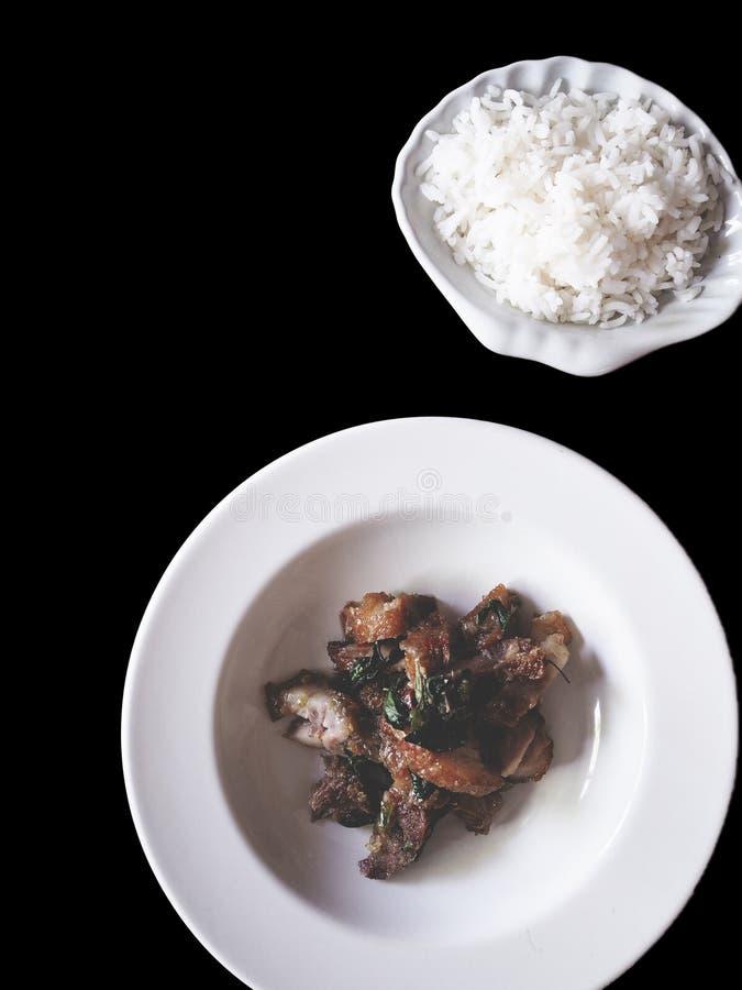 Le scalpore hanno fritto la carne di maiale croccante con basilico tailandese sul nero isolato immagine stock