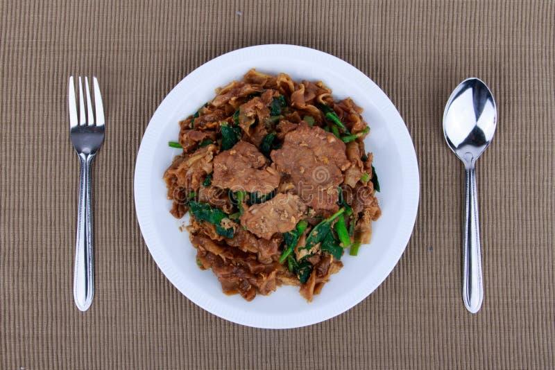 Le scalpore hanno fritto la tagliatella e la carne di maiale piane con la salsa di soia scura fotografie stock