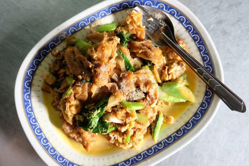 Le scalpore hanno fritto le tagliatelle e la carne di maiale piane con la salsa di soia scura immagine stock