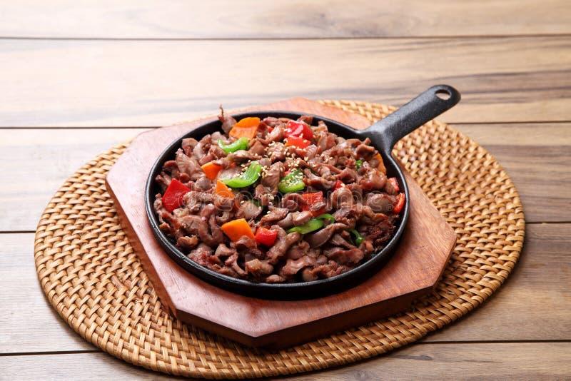 Le scalpore piccanti hanno fritto la carne di maiale nello stile del ttongjip di Korena sul taglio di legno fotografie stock
