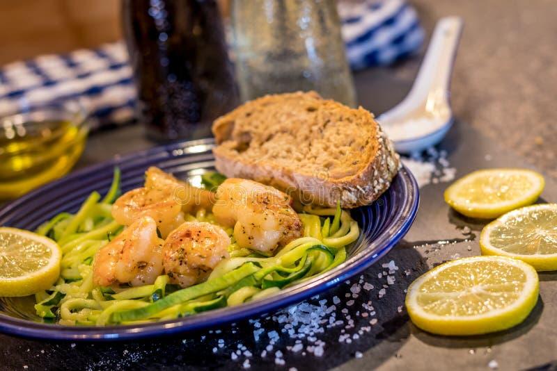 Le scampi de crevette a servi au-dessus des nouilles de courgette faites sauter avec le citron, l'ail, le beurre et les herbes photographie stock libre de droits