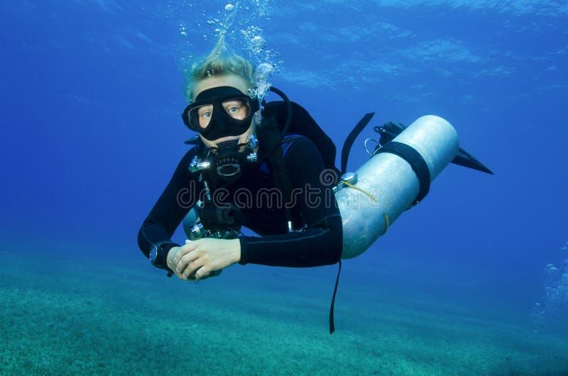 Le scaphandre latéral de bâti plonge dans l'eau bleue claire photographie stock
