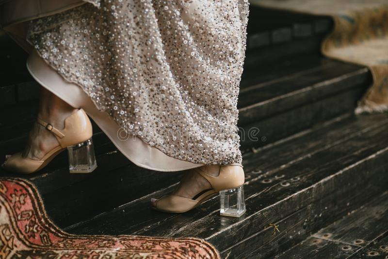 Le scarpe beige con un tallone trasparente sulle gambe del ` s della sposa vanno lungo la scala di legno, vestito da sera con ric fotografia stock