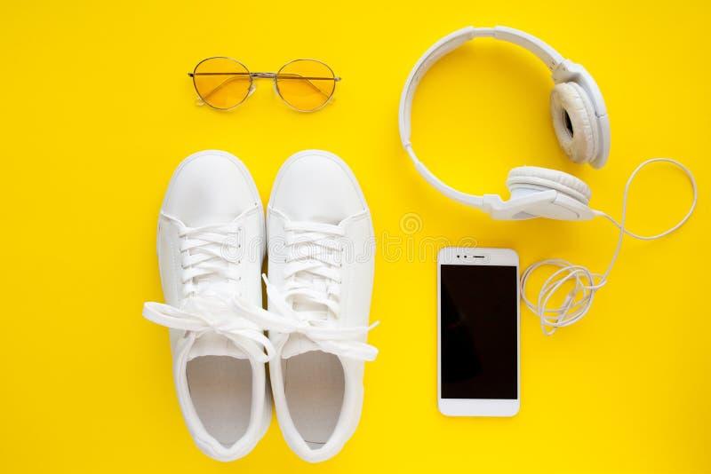 Le scarpe da tennis bianche, gli occhiali da sole rosa, le cuffie bianche e lo smartphone stanno trovando su un fondo giallo lumi immagine stock
