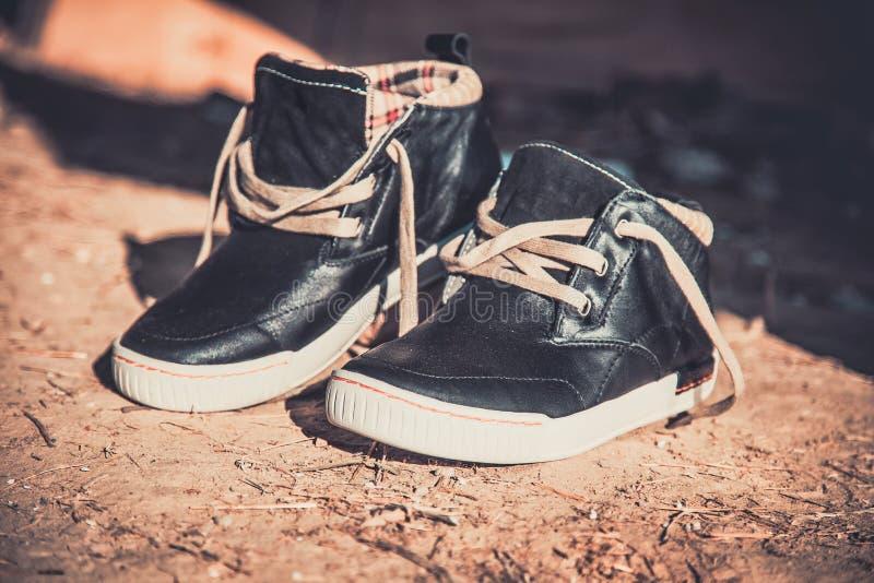 Le scarpe da tennis degli uomini nella polvere sull'asfalto immagine stock