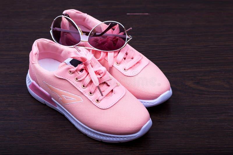 Le scarpe da tennis rosa delle donne su un fondo marrone punti nel telaio bianco Metta in mostra i pattini Calzature di modo Il t immagine stock