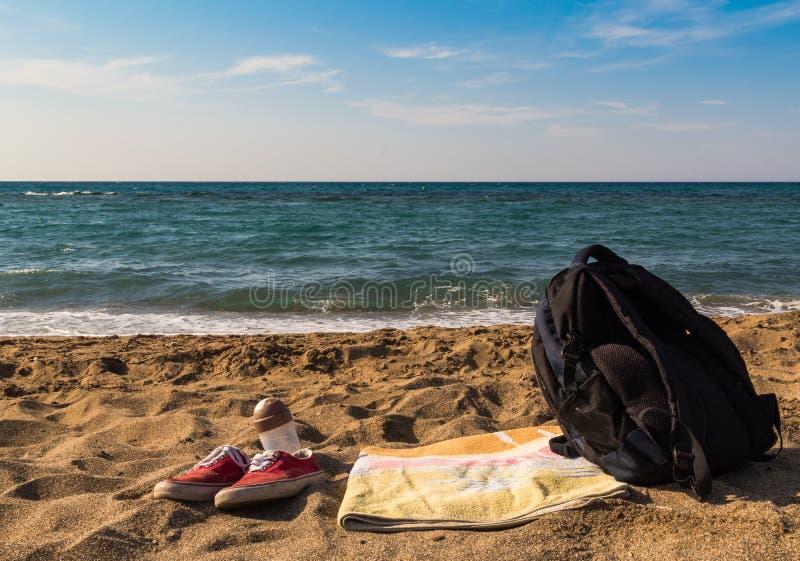 Le scarpe da tennis rosse asciugamano e zaino delle scarpe hanno andato sulla spiaggia dal mare Funzioni al mare fuga per un tuff fotografia stock libera da diritti